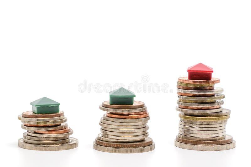 Il mini modello della casa su soldi conia su fondo bianco fotografia stock libera da diritti