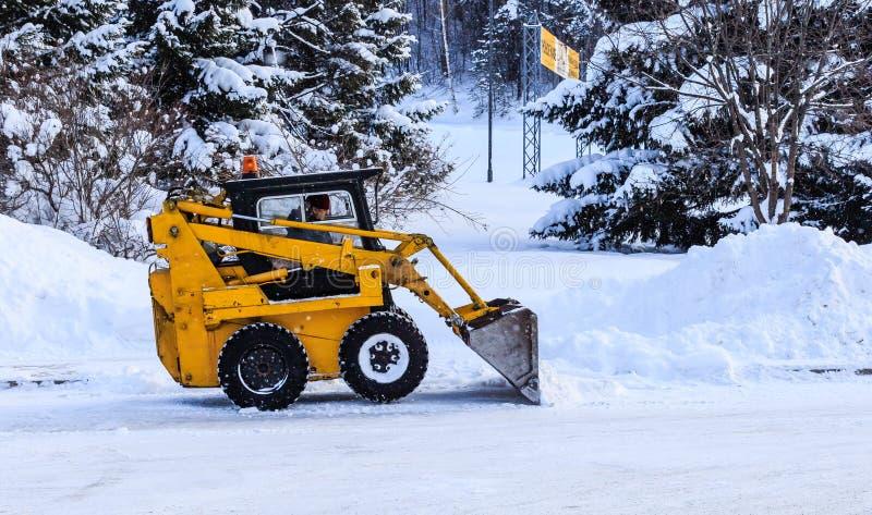 Il mini trattore rimuove la neve sulle vie della città fotografia stock libera da diritti