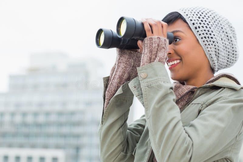 Il modello abbastanza giovane nell'inverno copre la sorveglianza della città con il binocolo immagine stock libera da diritti