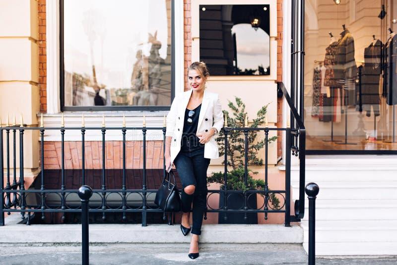 Il modello attraente in rivestimento bianco sui talloni sta appoggiandosi il recinto sul fondo del negozio Tiene la mano in tasca fotografia stock