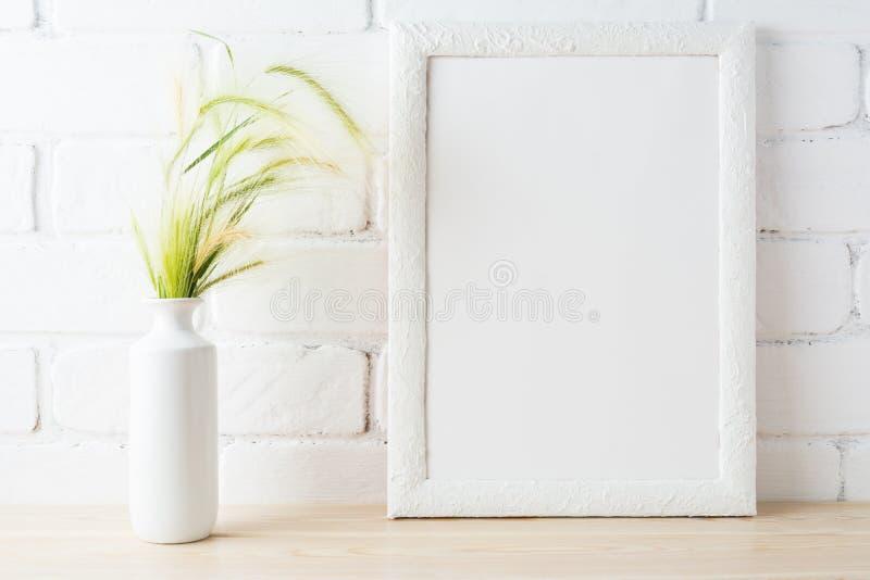 Il modello bianco della struttura con le orecchie dell'erba selvatica vicino ha dipinto il muro di mattoni fotografia stock