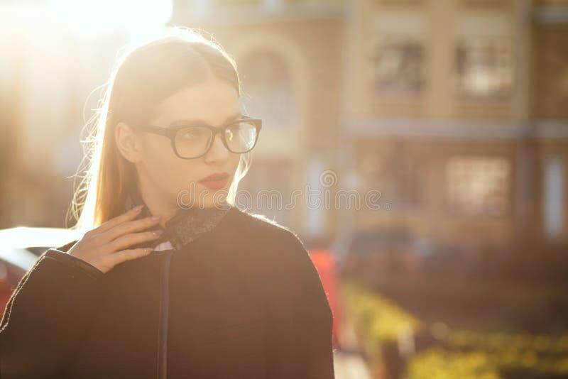 Il modello biondo alla moda indossa i vetri e la camminata giù la via soleggiata Spazio vuoto fotografia stock libera da diritti