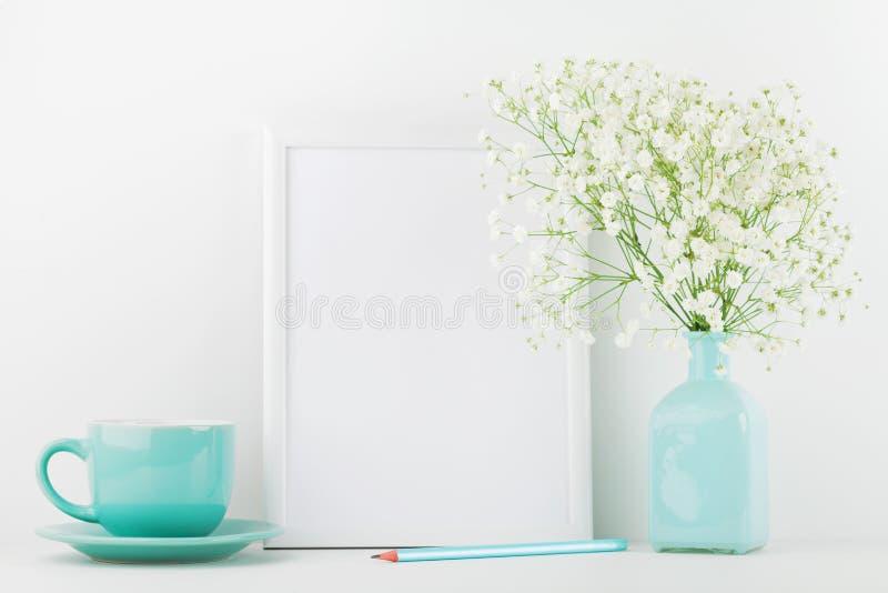 Il modello dei fiori decorati della cornice in tazza di caffè e del vaso sulla tavola bianca con spazio pulito per testo e proget immagini stock libere da diritti