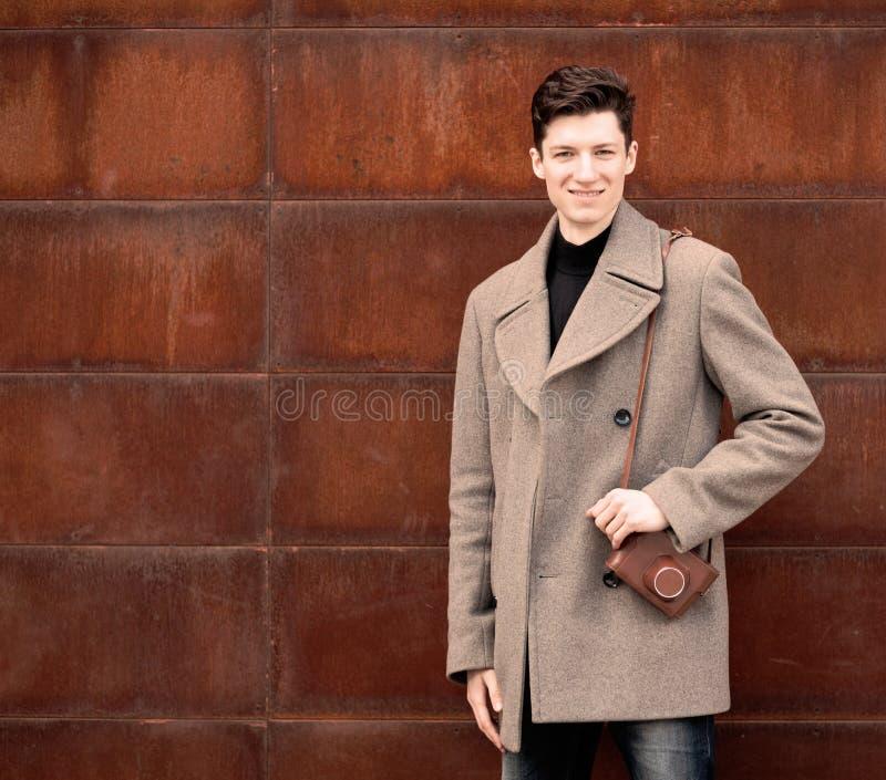 Il modello del giovane in un cappotto posa ad una parete arrugginita del metallo con la macchina fotografica d'annata su una spall fotografia stock