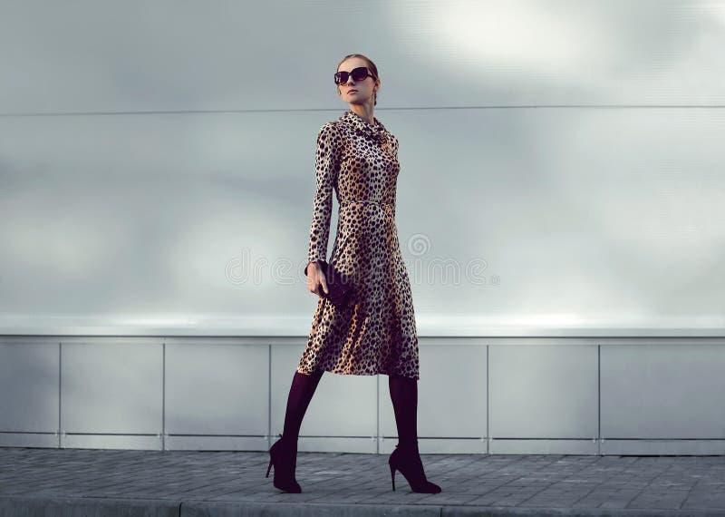 Il modello della donna di modo che porta un vestito dal leopardo sta camminando immagini stock