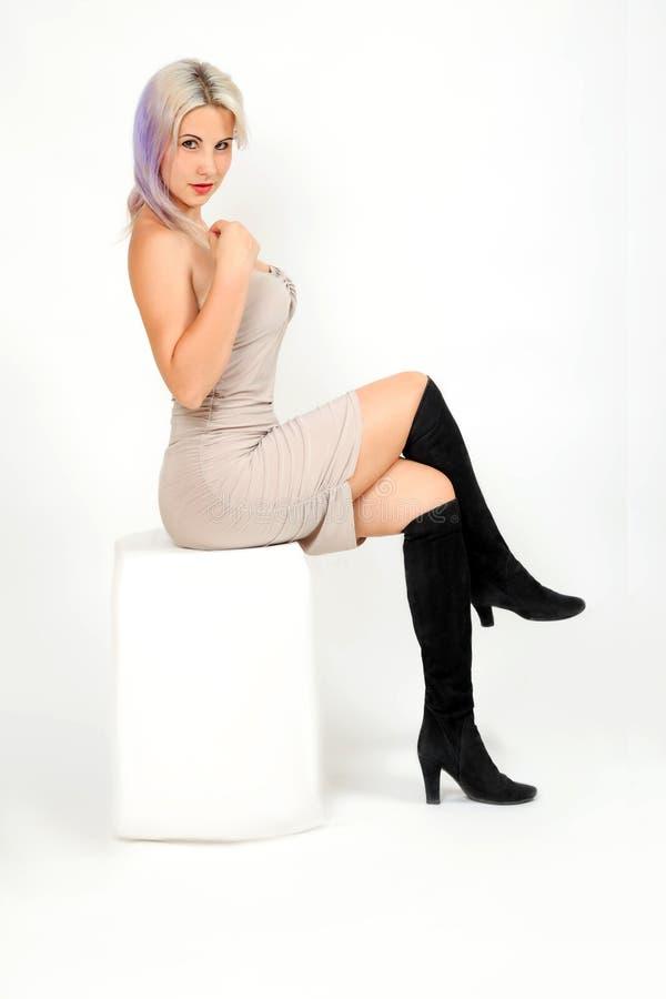 Il modello della donna si siede sul cubo bianco immagini stock