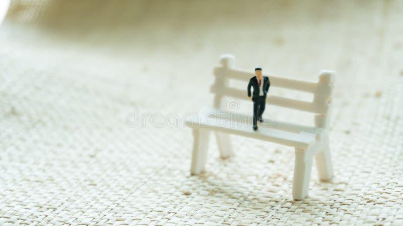 Il modello della figurina si siede sul banco come pensare immagini stock libere da diritti