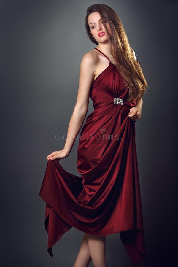 Il modello di moda elegante posa con il vestito rosso di seta fotografia stock