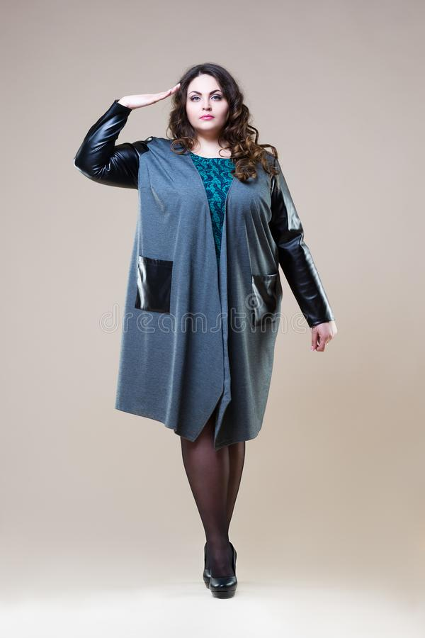 Il modello di moda più di dimensione saluta in abbigliamento casual, la donna grassa sul fondo beige dello studio, ente femminile fotografia stock libera da diritti