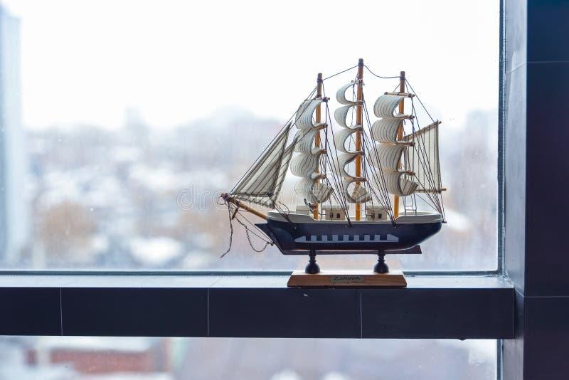 Il modello di una nave di navigazione sta su una finestra appannata Il concetto del viaggio Sogni di una vacanza immagine stock