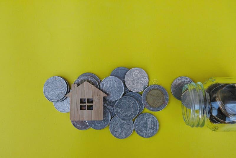 Il modello e le monete di legno della casa si sono sparsi fuori dal barattolo di vetro su fondo giallo-chiaro Investimento della  fotografie stock libere da diritti