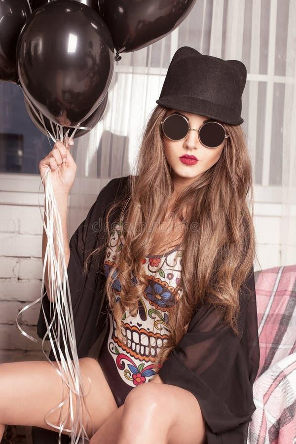 Il modello elegante della ragazza posa in associazione, vetri e cappello di giocatore di bocce Donna che tiene i baloons di un og immagini stock libere da diritti