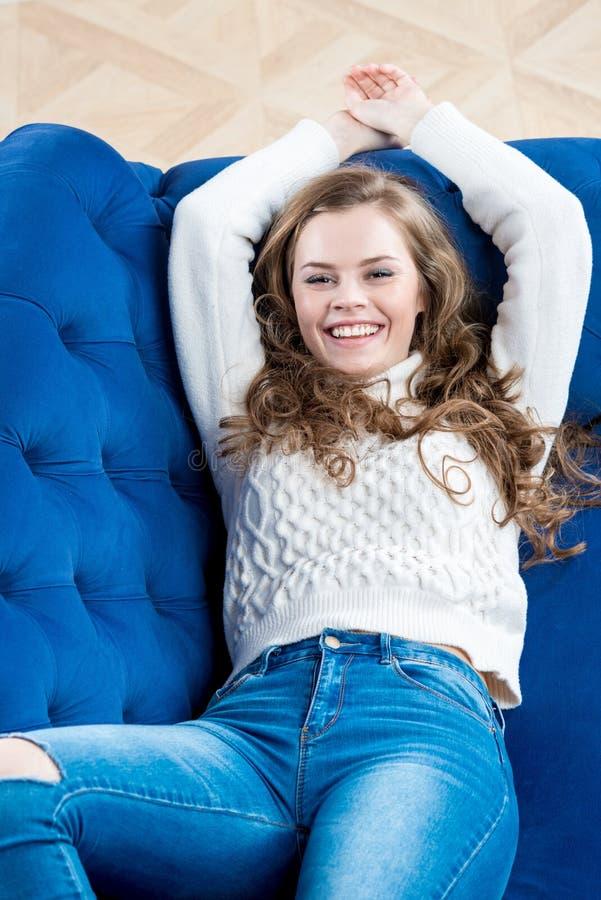 Il modello esile felice in maglione e jeans si rilassa immagini stock libere da diritti