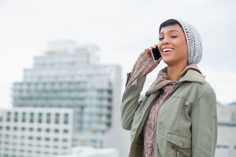 Il modello giovane di risata nell'inverno copre la risposta del suo telefono fotografie stock libere da diritti