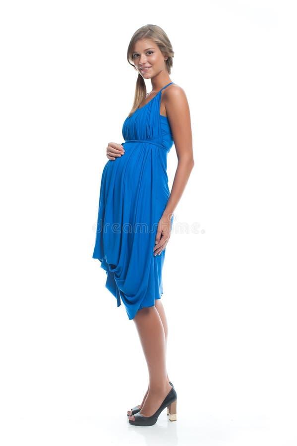 Il modello incinto della bella donna in vestito blu su bianco ha isolato la posa del fondo Vestiti per le donne incinte immagini stock