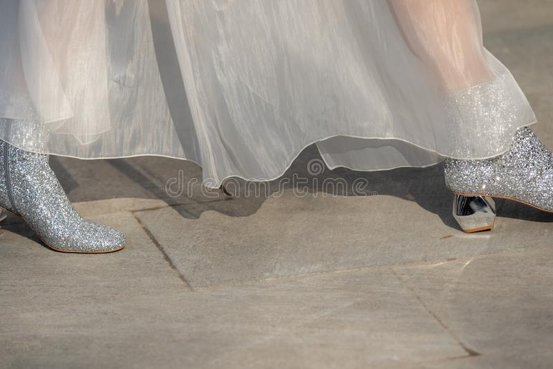 Il modello indossa un paio delle scarpe luccicanti e di un tacco alto d'argento di alto-lucentezza fotografia stock
