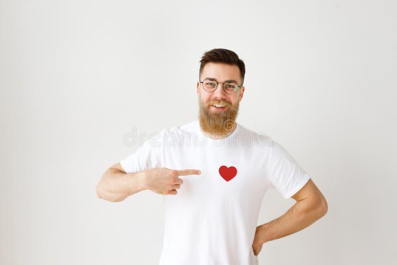Il modello maschio barbuto sorridente felice porta la maglietta bianca casuale, occhiali rotondi, indica a cuore rosso cucito sui immagine stock