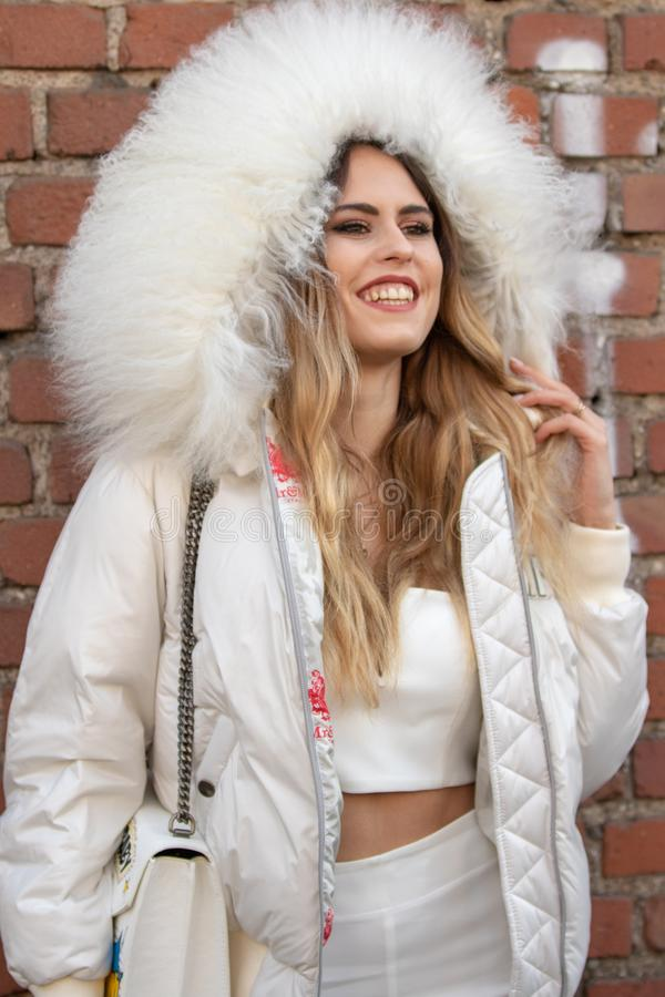 Il modello porta una cima bianca e un rivestimento bianco con un cappuccio voluminoso immagine stock libera da diritti