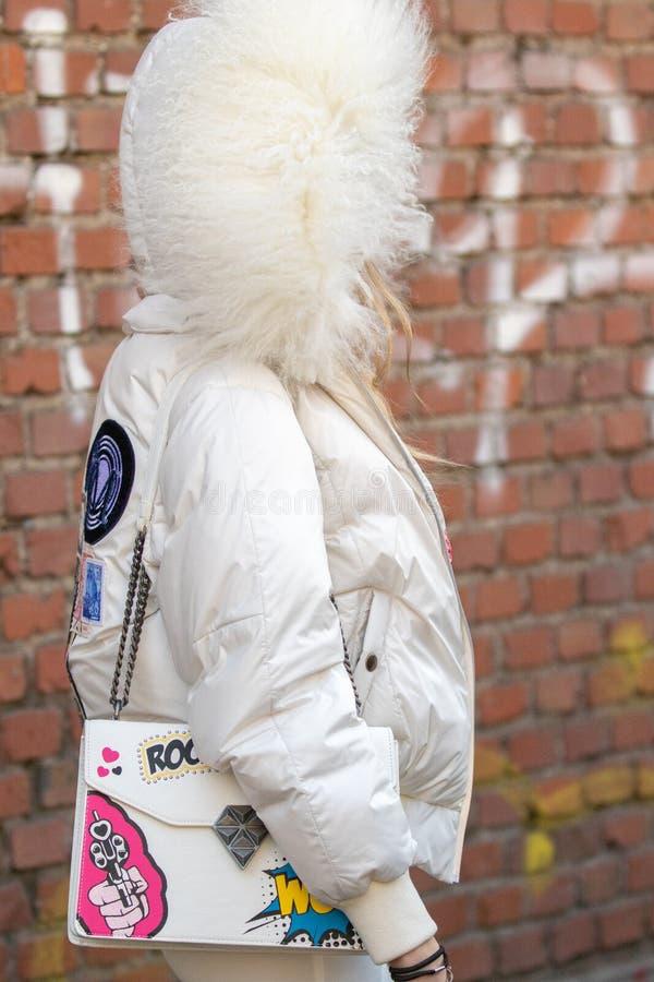 Il modello porta una cima bianca e un rivestimento bianco con un cappuccio voluminoso fotografia stock