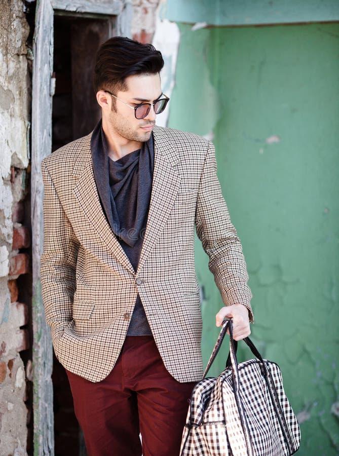Il modello sexy dell'uomo di modo ha vestito la tenuta elegante una posa della borsa fotografia stock
