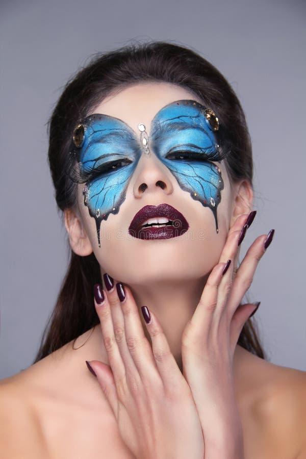 Il modo compone. Trucco della farfalla sulla bella donna del fronte. Arte P fotografie stock libere da diritti