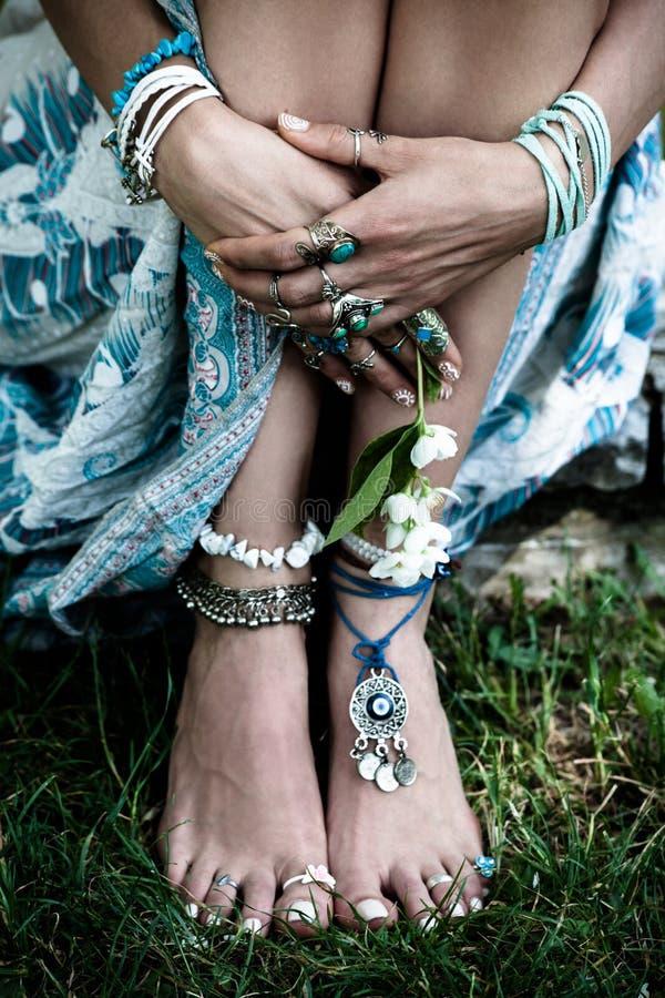 Il modo di Boho dettaglia le mani della donna ed i piedi nudi su erba con il lotto immagini stock libere da diritti