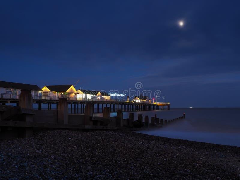 Il molo di Southwold si illuminò di notte accanto a un becco di legno sotto una luna brillante con una nave all'orizzonte, Suffol fotografia stock libera da diritti