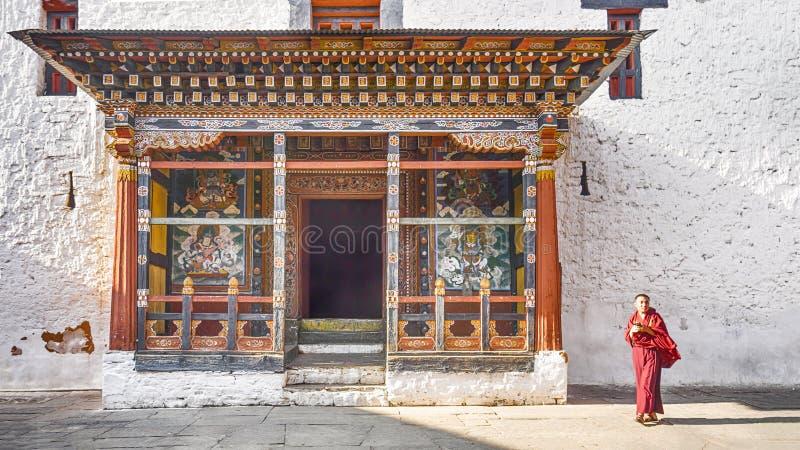 Il monaco dell'uomo dell'Asia cammina vicino alla preghiera della torre della porta principale a Paro Dzong, fotografia stock libera da diritti
