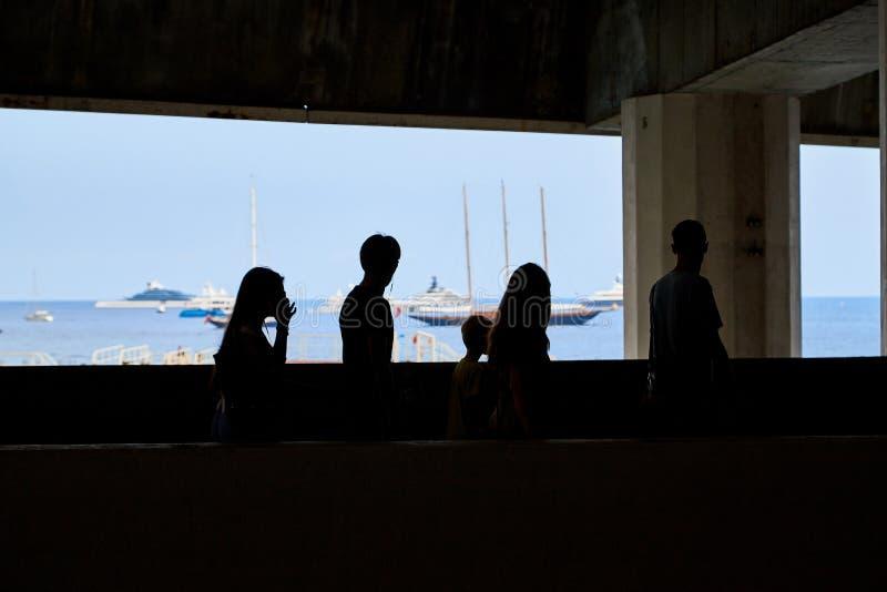 Il Monaco, Monte Carlo - 23 settembre 2018: Siluette scure della gente davanti alla finestra con il mare e le navi blu fotografia stock libera da diritti