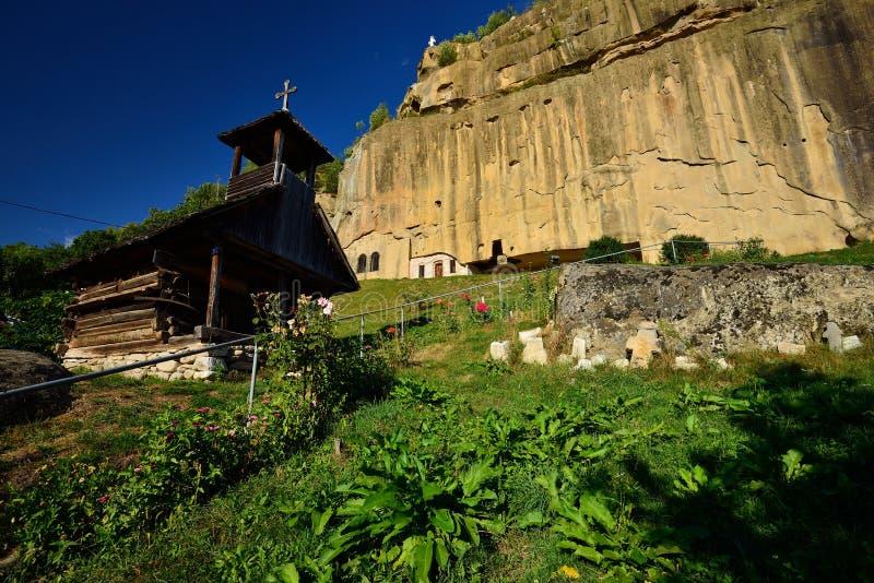Il monastero di pietra di Ravens (Corbii de piatra) e la chiesa di legno da Corbi, contea di Arges, Romania fotografie stock