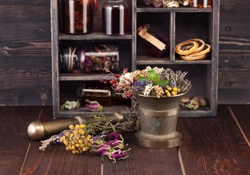Il mortaio con le erbe mediche, la tintura imbottiglia una scatola di legno fotografia stock libera da diritti