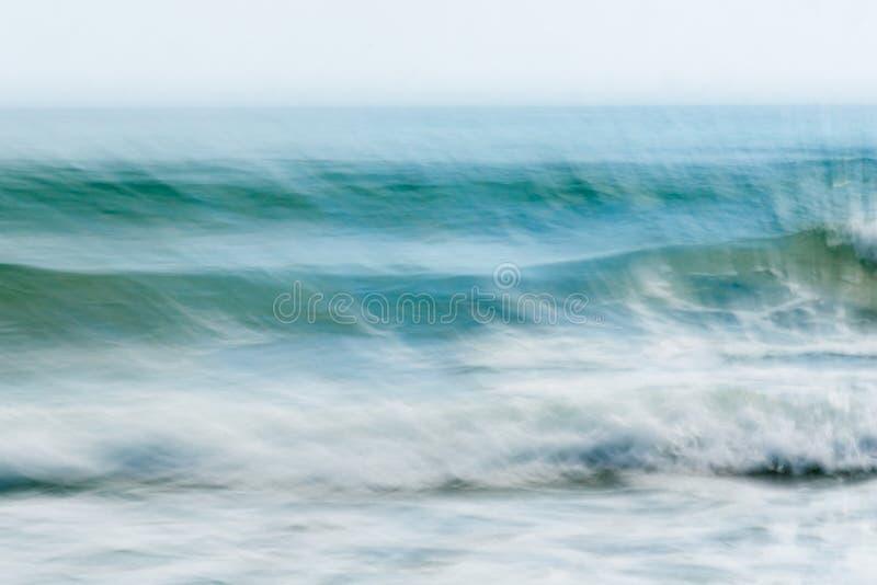 Il moto astratto costiero ha offuscato il backgroun dei toni del blu delle onde di oceano immagine stock