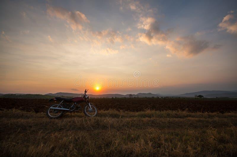 Il motobike sul campo, tramonto in paese e nuvola beatyful sulla città di Dalat del cielo - in LamDong- Vietnam immagini stock