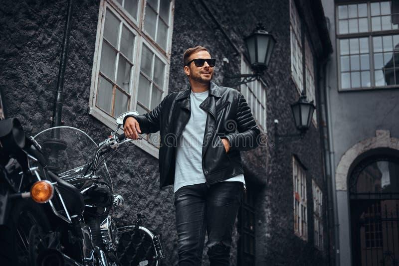 Il motociclista alla moda in occhiali da sole si è vestito in bomber nero e jeans che si appoggiano il suo retro motociclo su un  immagini stock libere da diritti
