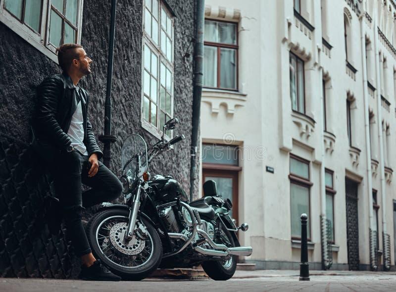 Il motociclista alla moda si è vestito in bomber nero e jeans che si appoggiano una parete vicino al suo retro motociclo su vecch immagini stock libere da diritti