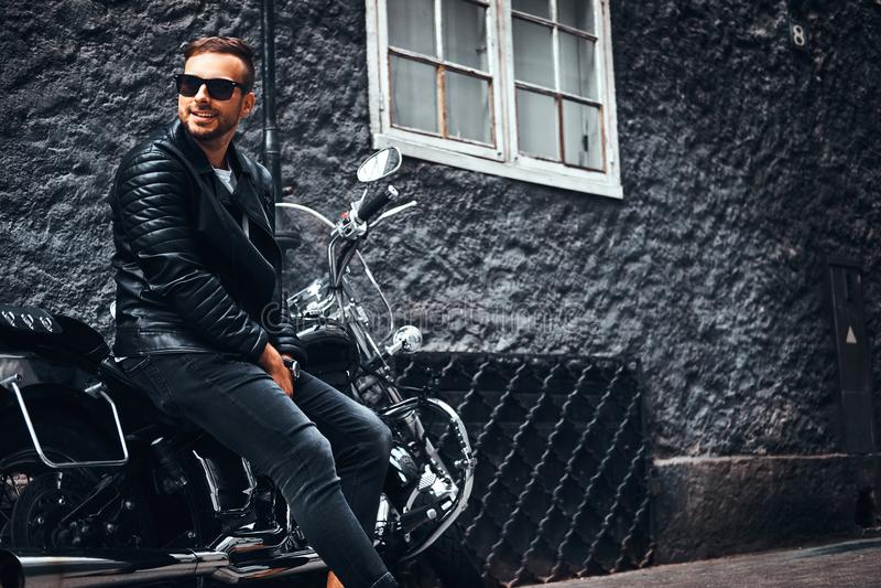 Il motociclista alla moda si è vestito in bomber nero e jeans che si siedono sul suo retro motociclo su una vecchia via di Europa immagine stock libera da diritti