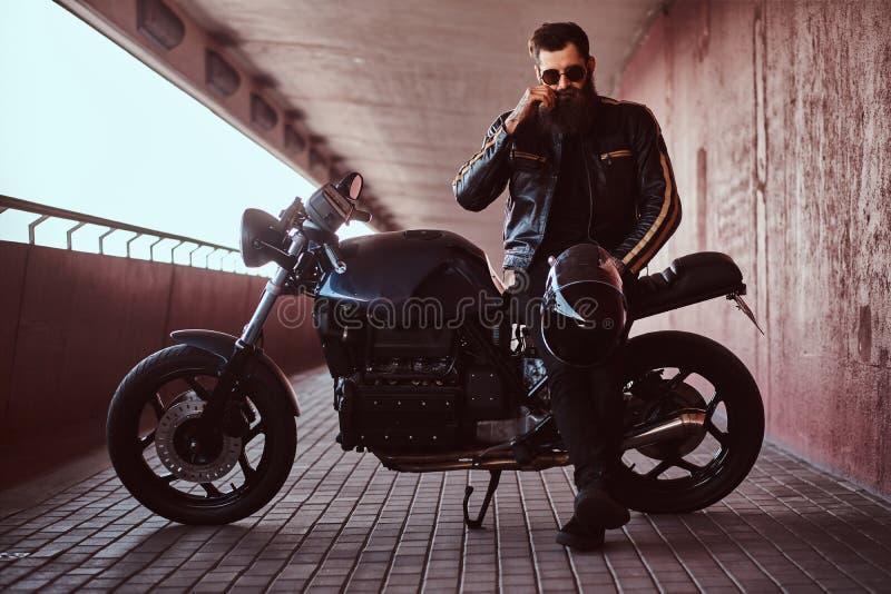 Il motociclista alla moda alla moda si è vestito in un bomber nero con gli occhiali da sole ripara i baffi e tiene il casco mentr immagini stock