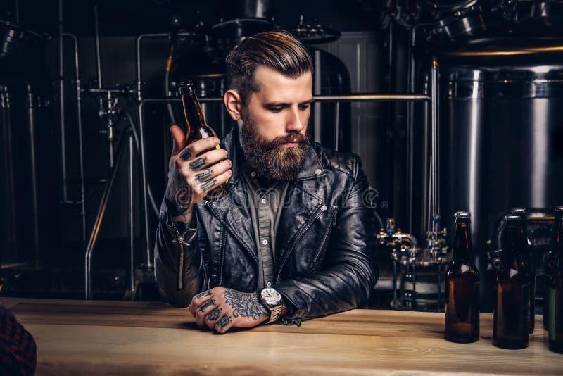 Il motociclista barbuto alla moda ha vestito il bomber nero che si siede al contatore della barra in fabbrica di birra indipenden fotografia stock libera da diritti