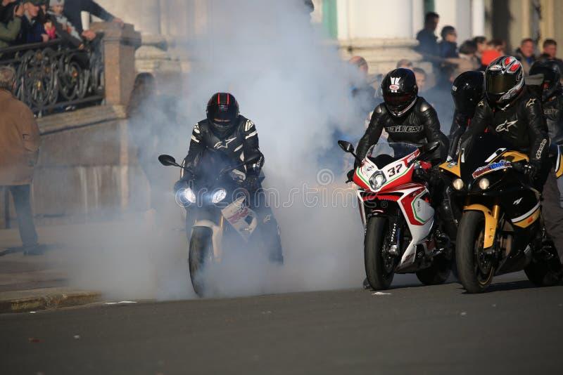 Il motociclista brucia la gomma della sua bici in una nuvola di fumo fotografia stock