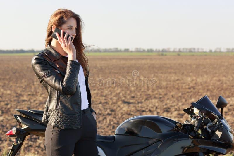 Il motociclista femminile ha conversazione telefonica, si ferma sulla strada, posa vicino alla motocicletta, ultime notizie dei d fotografia stock