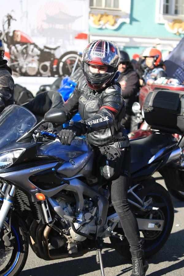 Il motociclista femminile si siede sul suo motociclo di Yamaha fotografia stock