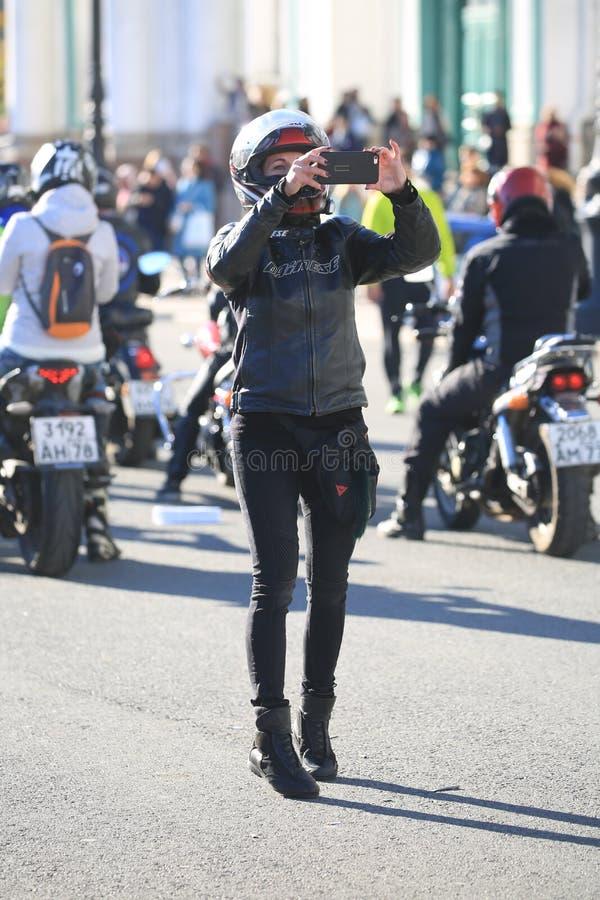 Il motociclista femminile spara un evento sul suo smartphone un giorno soleggiato immagine stock