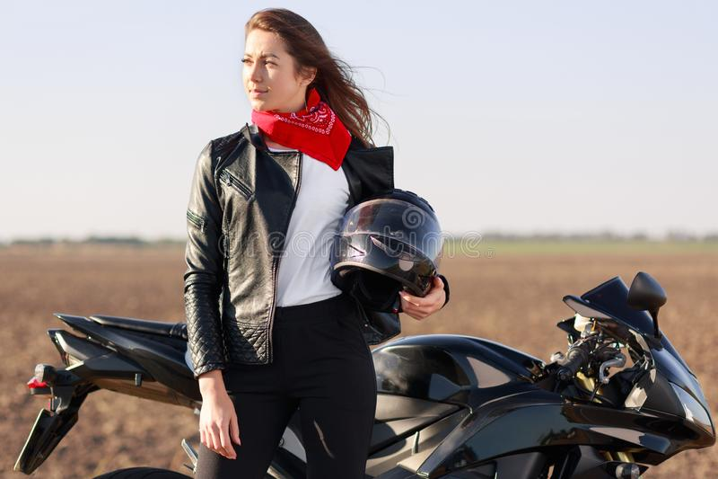 Il motociclista femminile spensierato rilassato guarda meditatamente da parte, porta il casco, vestito in bomber nero, supporti v immagine stock libera da diritti