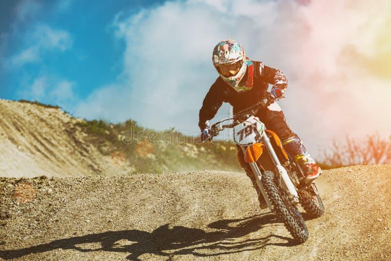 Il motociclista guida sulla strada nelle alte montagne delle dune di sabbia cielo blu del fondo con le nuvole fotografia stock libera da diritti