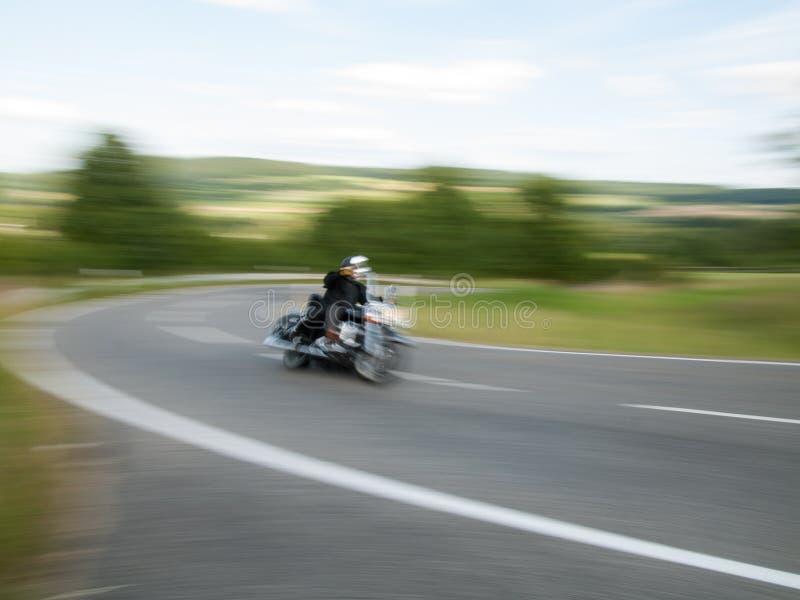 Il motociclista passa in salita attraverso la curva, mosso 2 fotografie stock libere da diritti