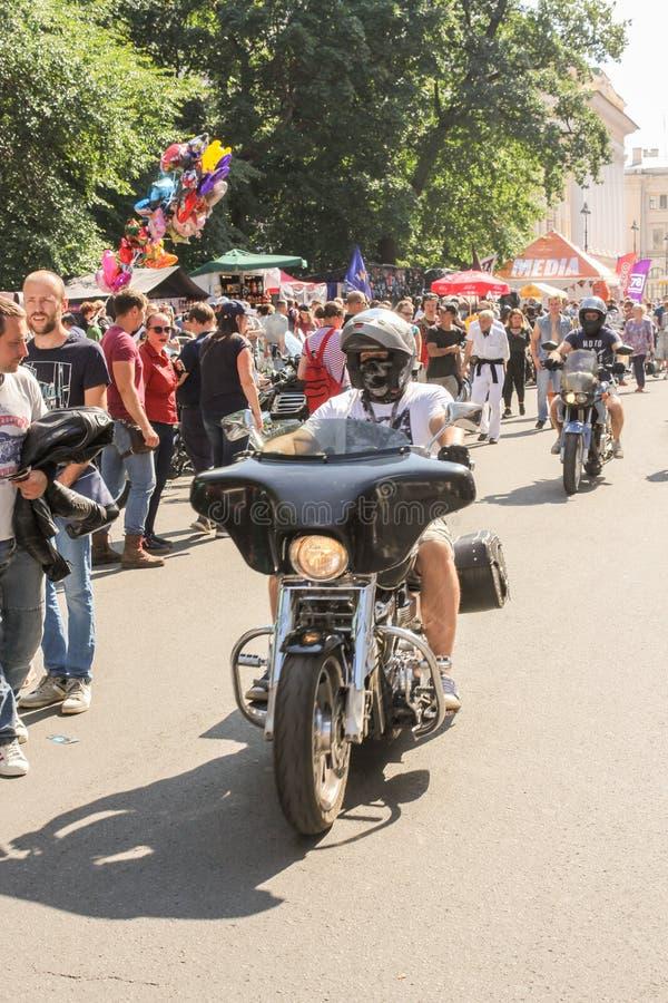 Il motociclista sta guidando un motociclo dopo la gente immagini stock