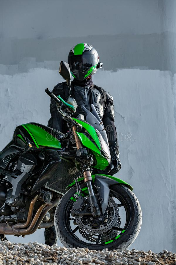 Il motociclista in un casco ed in un vestito protettivo sta sotto il ponte immagini stock
