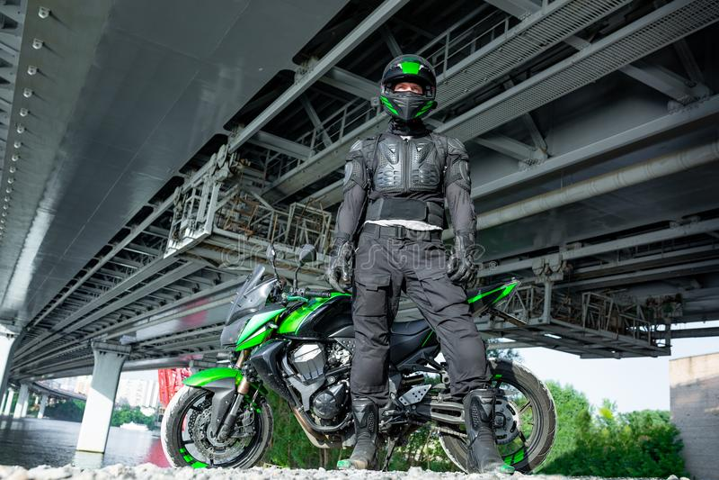 Il motociclista in un casco ed in un vestito protettivo sta sotto il ponte fotografia stock libera da diritti