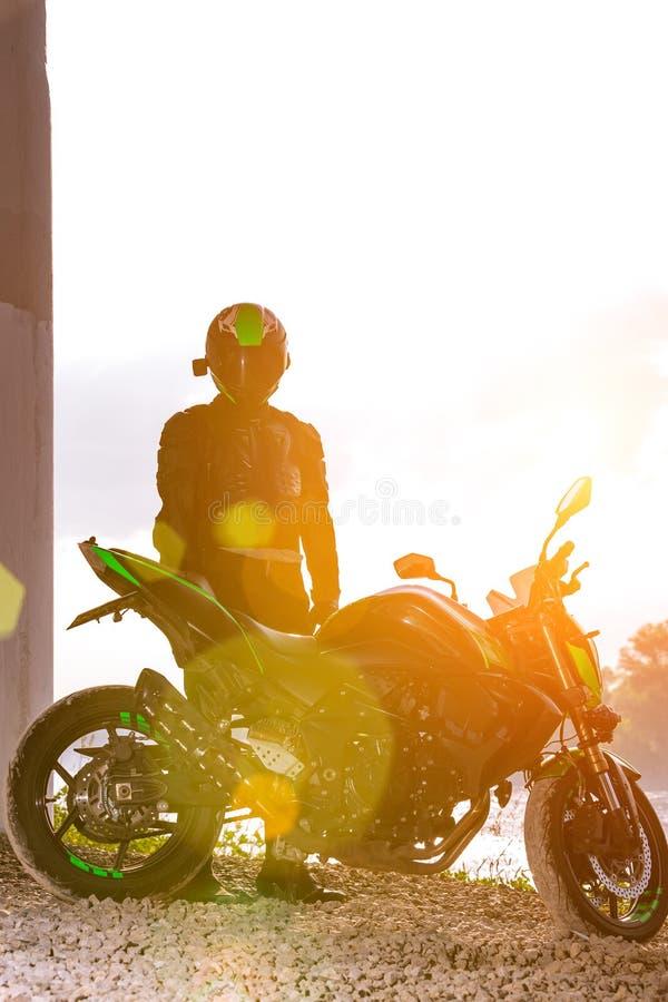 Il motociclista in un casco ed in un vestito protettivo sta sotto il ponte fotografie stock libere da diritti