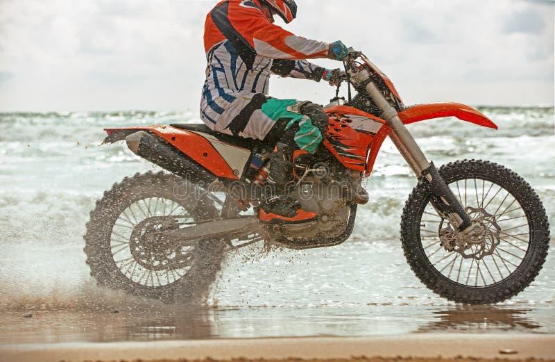 Il motociclista in un vestito protettivo guida un motociclo sul mare, spruzza la mosca da sotto le ruote fotografia stock libera da diritti